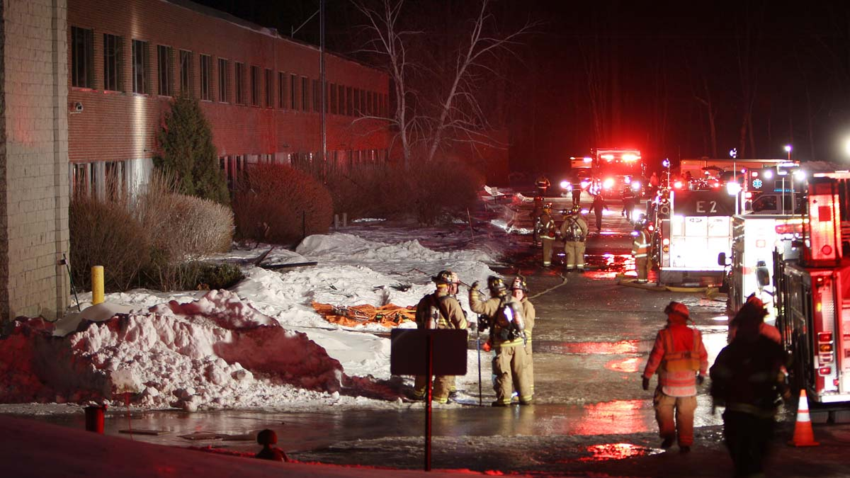 Emergency crews from several towns work an area outside the New Hampshire Ball Bearing plant after an explosion, Monday, Feb. 10, 2014 in Peterborough, N.H. At least 13 people were injured, but a company spokeswoman says none of the injuries appears to be life-threatening.