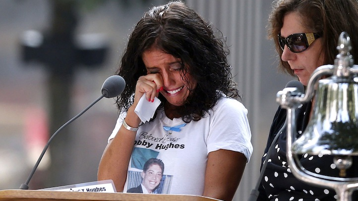 A woman wipes her eyes after reading the name of her brother, Bobby Hughes, as friends and relatives of the victims of the 9/11 terrorist attacks gather at the National September 11 Memorial at the World Trade Center site 12 years after the tragic day. The anniversary was marked with events in New York, Washington, Shanksville, Pa. Click to see more pictures of the 9/11 ceremonies.