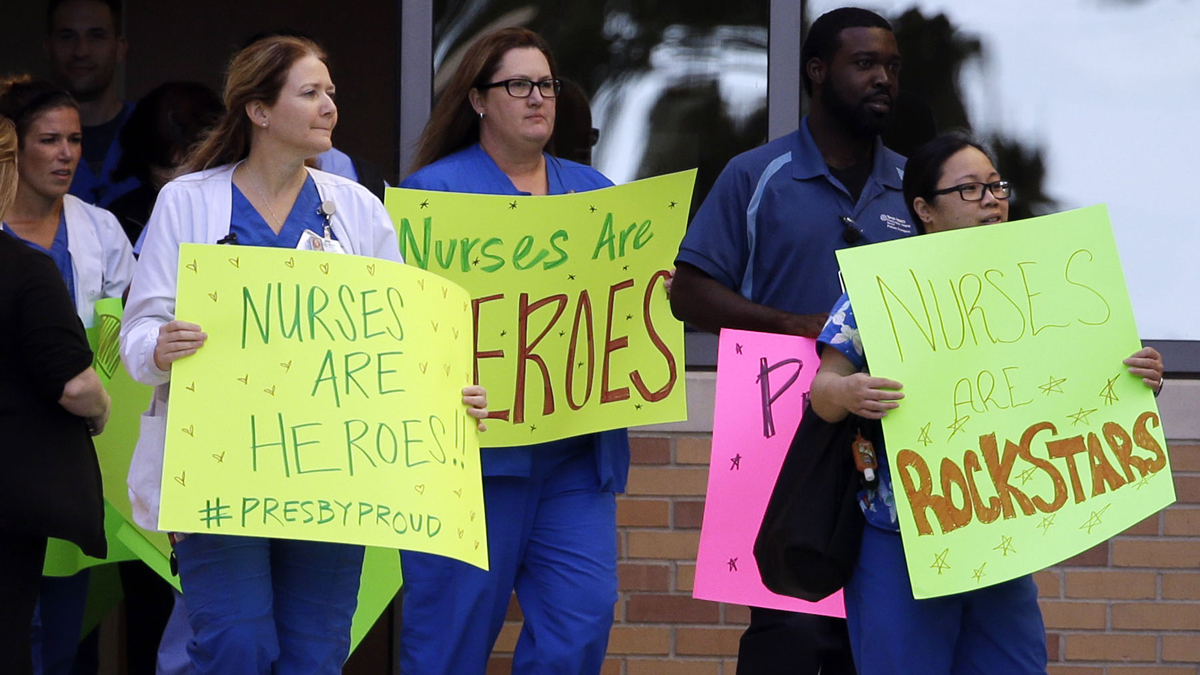 Texas Health Presbyterian Hospital Dallas staff line the drive that exits the emergency room as they wait for an ambulance carrying Nina Pham to depart, Thursday, Oct. 16, 2014, in Dallas, Texas.