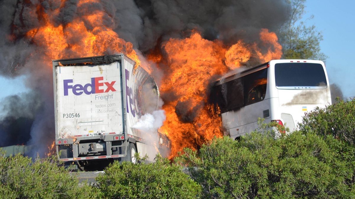 Massive flames engulf a tractor-trailer and a tour bus just after they collide on Interstate 5, Thursday, April, 10, 2014, near Orland, Calif. At least 10 people were killed in the crash, authorities said. (AP Photo/Jeremy Lockett)