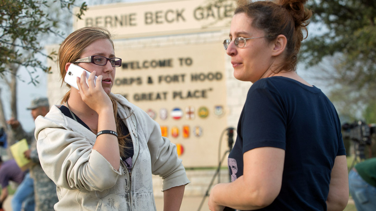 Krystina Cassidy and Dianna Simpson attempt to make contact with their husbands who are stationed inside Fort Hood, while standing outside of the Bernie Beck Gate, on Wednesday, April 2, 2014, in Fort Hood, Texas. One person was killed and 14 injured in a shooting Wednesday at Fort Hood, and officials at the base said the shooter is believed to be dead. (AP Photo/ Tamir Kalifa)