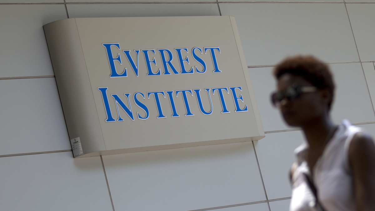 FILE - In this July 8, 2014 file photo, a woman walks past the Everest Institute in Silver Spring, Md. Corinthian Colleges, which owns Everest, Heald College and WyoTech schools, has announced it will shut down all of its remaining 28 ground campuses, displacing about 16,000 students.
