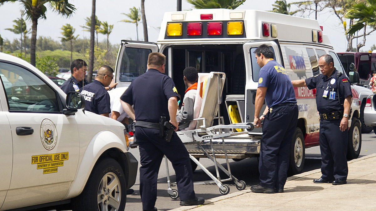 A 16-year-old boy, seen sitting on a stretcher center, who stowed away in the wheel well of a flight from San Jose, Calif., to Maui is loaded into an ambulance at Kahului Airport in Maui, Hawaii Sunday afternoon, April 20, 2014. The boy survived the trip halfway across the Pacific Ocean unharmed despite frigid temperatures at 38,000 feet and a lack of oxygen, FBI and airline officials said. FBI spokesman Tom Simon in Honolulu told The Associated Press on Sunday night that the boy was questioned by the FBI after being discovered on the tarmac at the Maui airport with no identification.