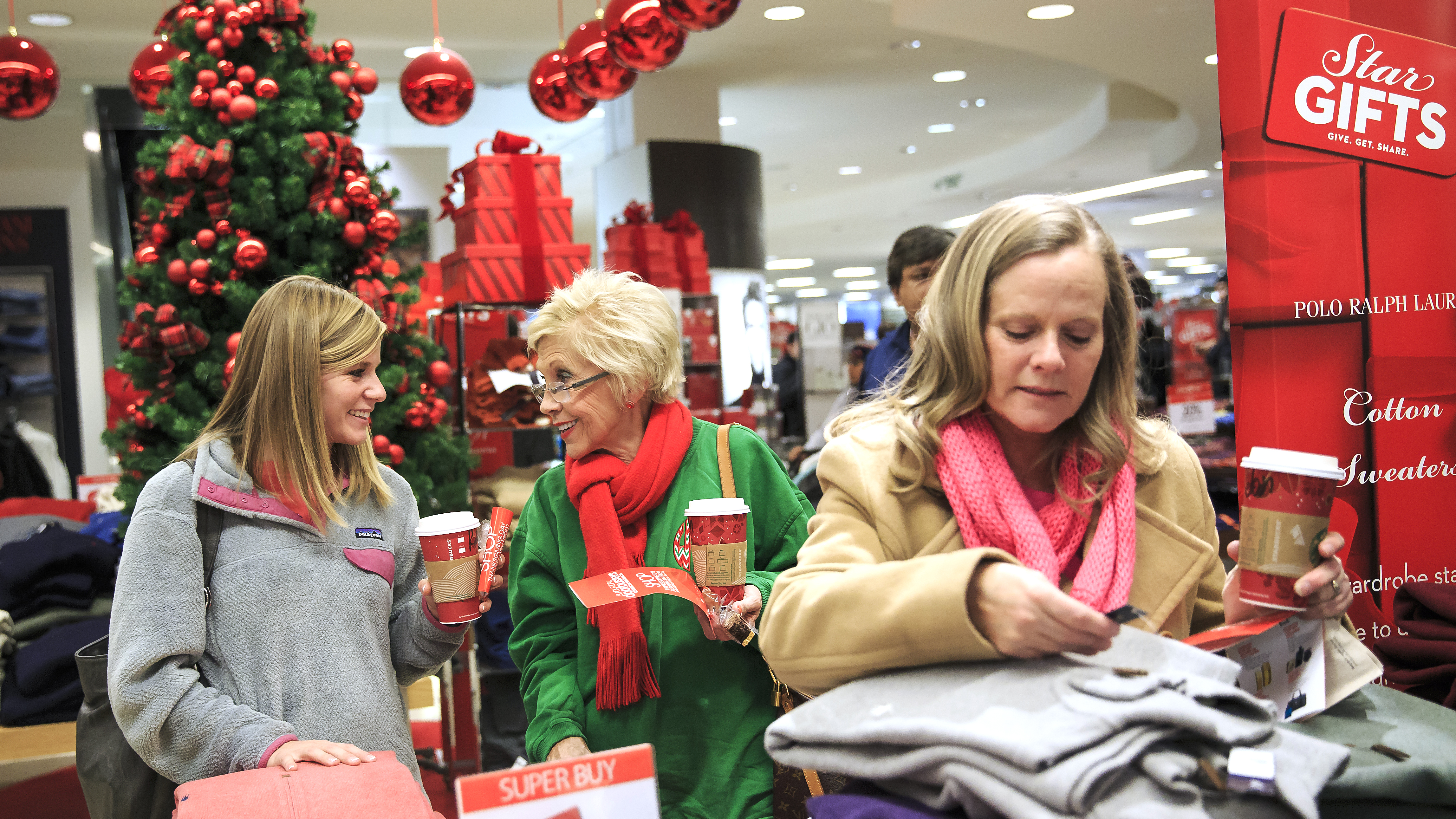 Jessica Gaddy reacts with Wanda Kemp as they shop during the Macy's Lenox Black Friday store opening on Thursday, November 28, 2013 in Atlanta.