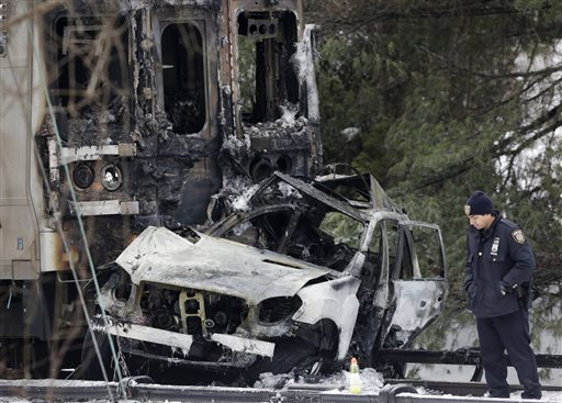 A police officer looks at a SUV that was crushed and burned at the front of a Metro-North Railroad train Wednesday, Feb. 4, 2015, in Valhalla, N.Y.  Five train passengers and the SUV's driver were killed in Tuesday evening's crash in Valhalla, about 20 miles north of New York City. Authorities said the impact was so forceful the electrified third rail came up and pierced the train.(AP Photo/Mark Lennihan)
