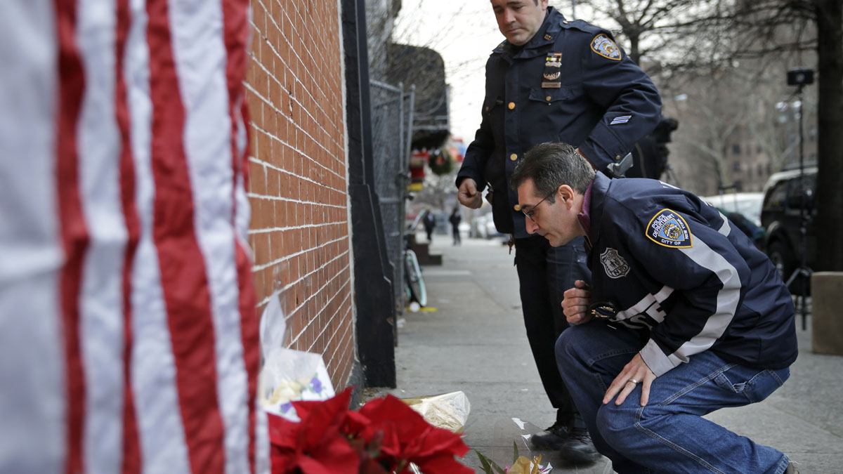 Police officers leave candles at an impromptu memorial near the site where two New York City police officers were killed in the Brooklyn borough of New York, Sunday, Dec. 21, 2014.