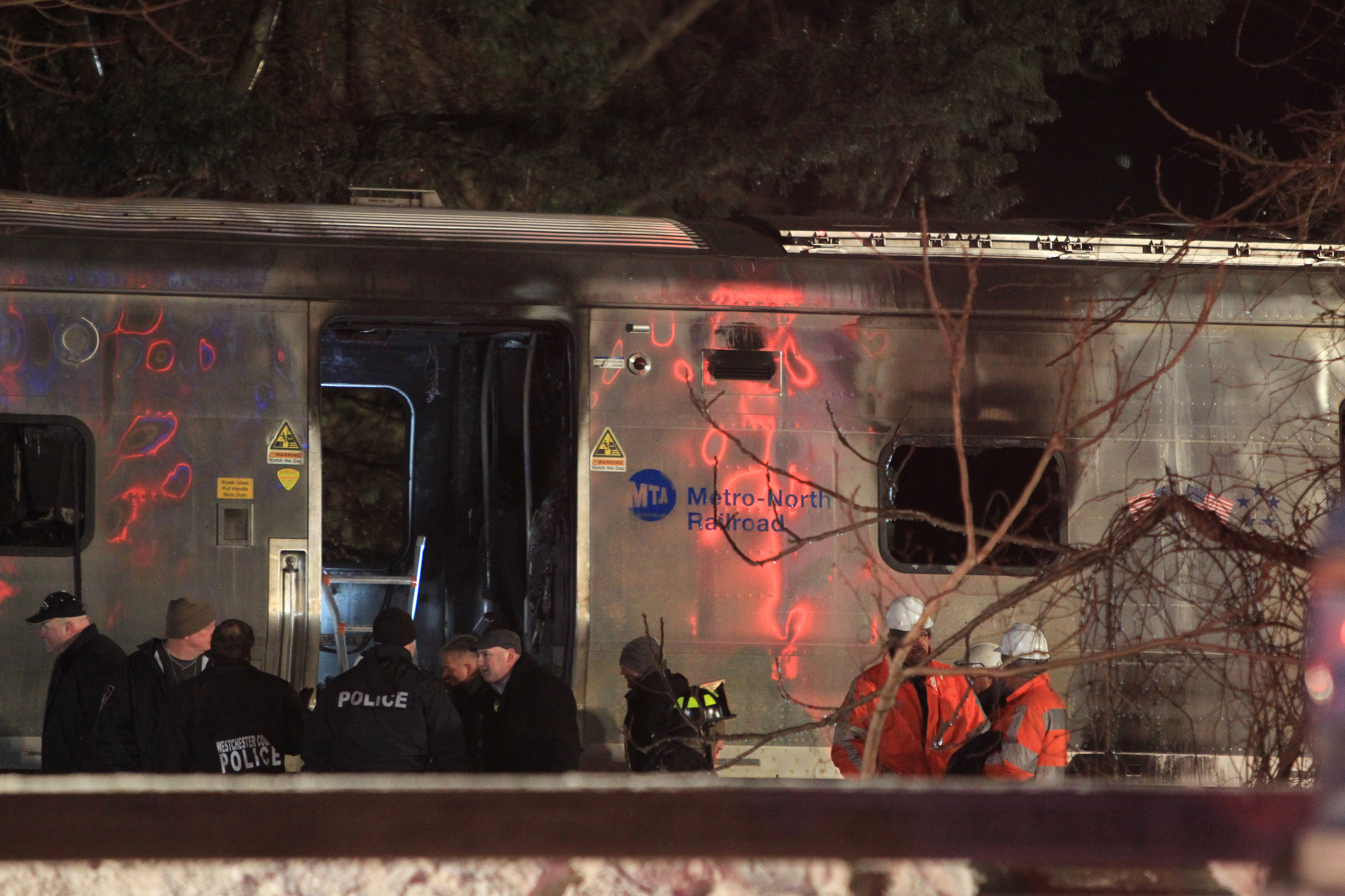 Emergency personnel work at the scene of a Metro-North Railroad passenger train and vehicle accident in Valhalla, N.Y., Tuesday, Feb. 3, 2015. Metro-North Railroad spokesman Aaron Donovan says the train struck a vehicle at a railroad crossing about 20 miles north of New York City. (AP Photo/Robert Mecea)