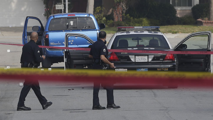 Bullet holes riddle a blue pickup truck in Torrance on Feb. 7, 2013. Two newspaper delivery women were traveling in the car when police officers mistook them for an ex-officer wanted in a deadly rampage.