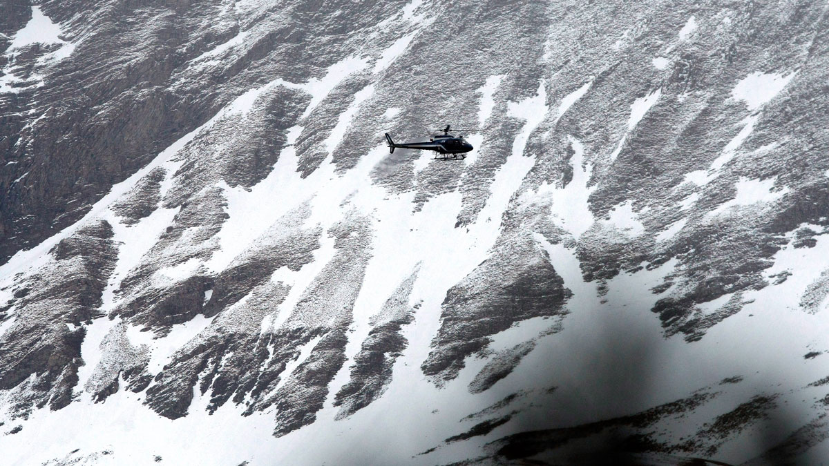 A rescue helicopter flies over the mountainside near Seyne-les-Alpes, French Alps, March 24, 2015.