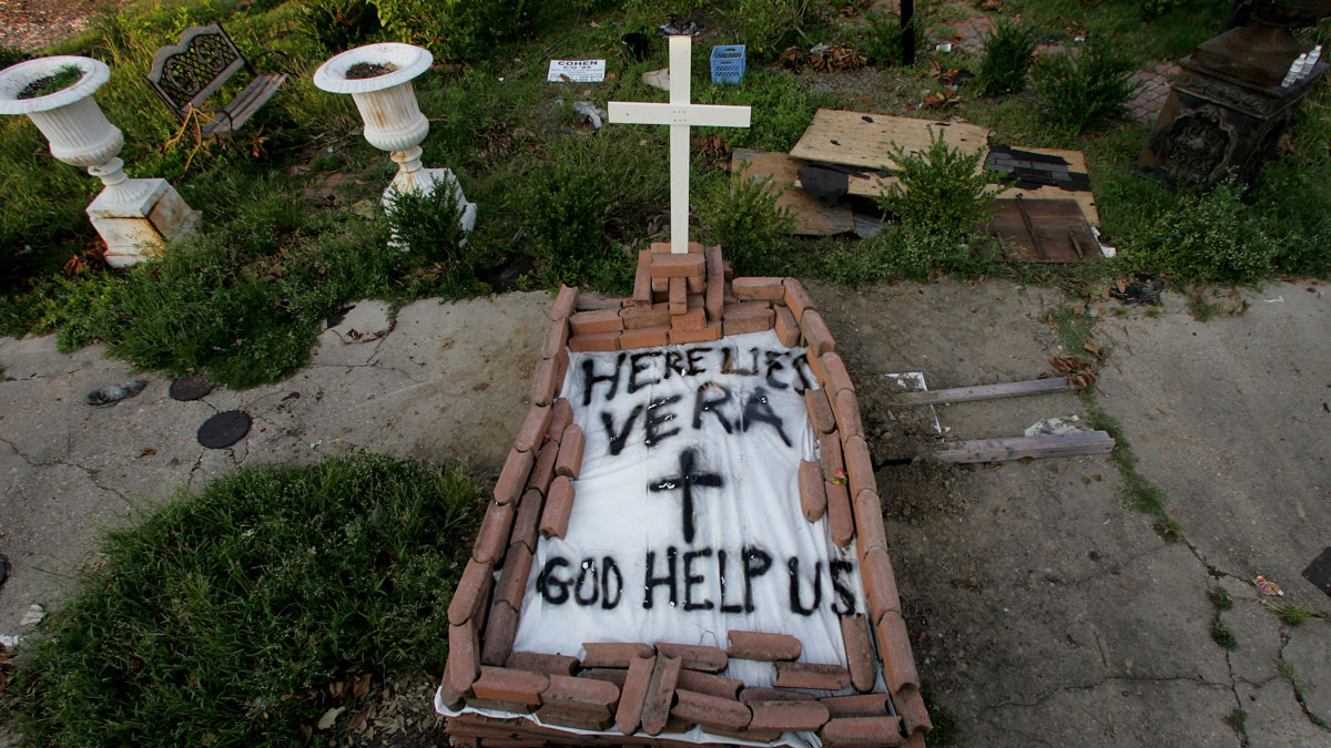 A makeshift tomb at a New Orleans street corner conceals a body that had been lying on the sidewalk for days in the wake of Hurricane Katrina on Sunday, Sept. 4, 2005.  The message reads,