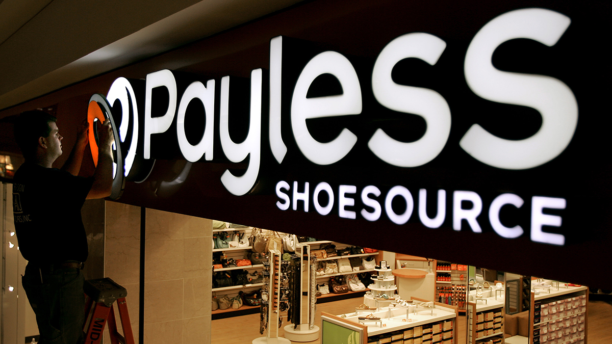 A worker puts the finishing touches on a sign unveiling the company's new look at a Payless Shoesource store at a mall in Independence, Missouri, in this May 18, 2006, file photo.