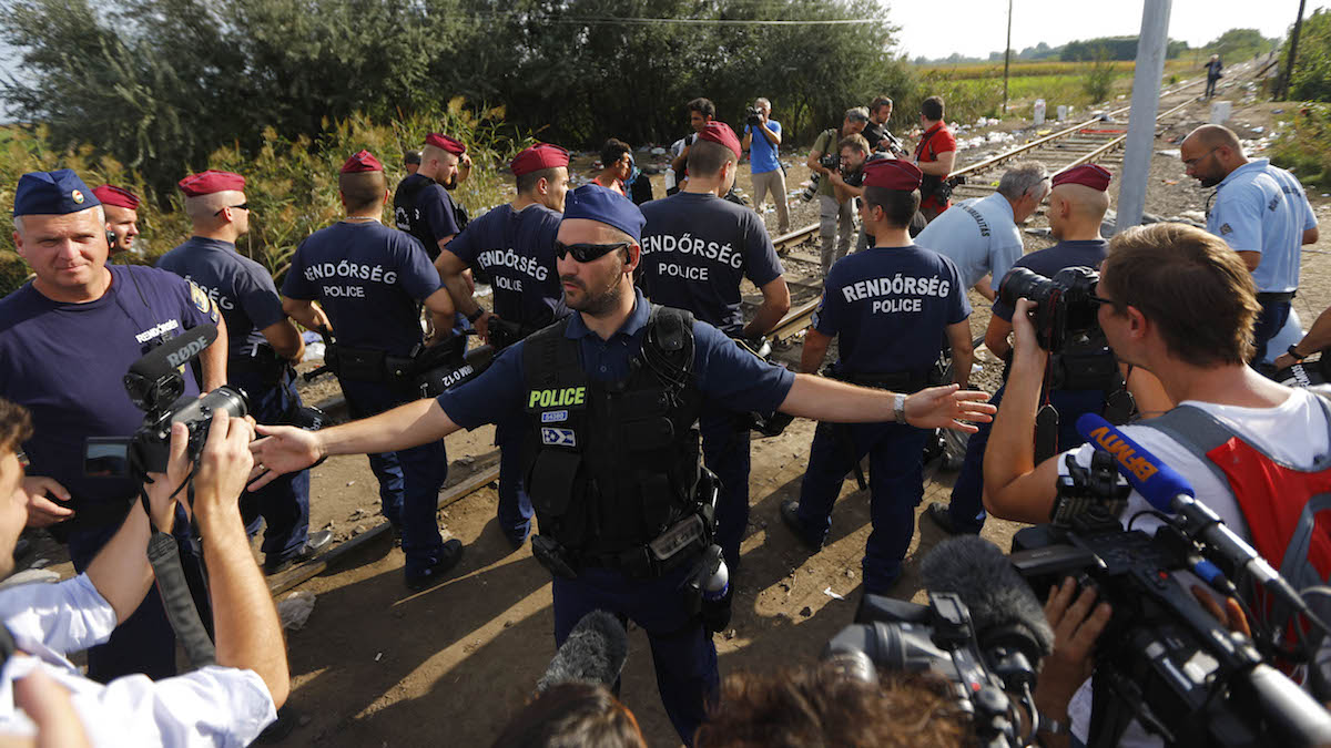 Hungarian police officers prepare to close the border line between Serbia and Hungary in Roszke, southern Hungary in Roszke, Monday, Sept. 14, 2015. Hungary, are set to introduce much harsher border controls at midnight — laws that would send smugglers to prison and deport migrants who cut under Hungary's new razor-wire border fence.