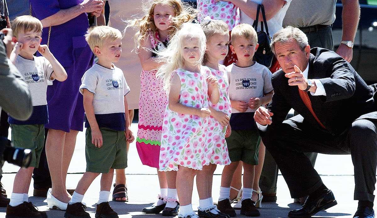 In this Aug. 14, 2002 file photo, President George Bush points out reporters and photographers to some of the McCaughey septuplets who greeted him on his arrival at the Des Moines International Airport in Des Moines, Iowa. The McCaughey septuplets, the world's first surviving septuplets, graduated from high school in Iowa on May 22.