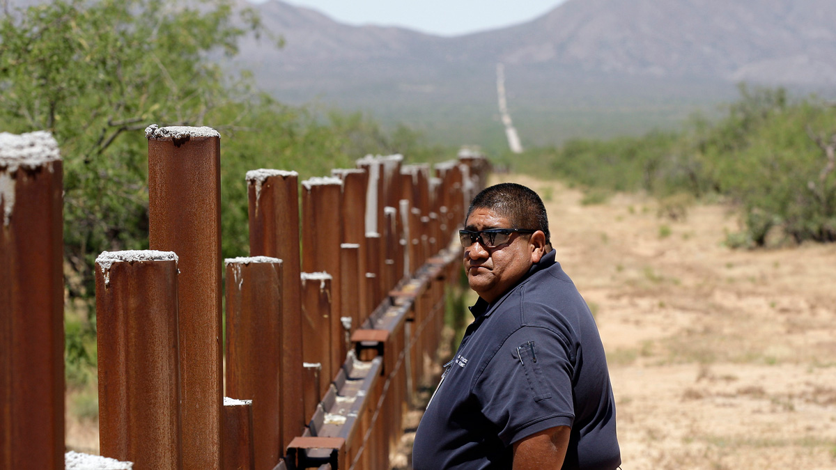 In this May 13, 2010 photo, Tohono O'odham Nation Police Sgt. Vincent Garcia walks along the new border fence at the U.S.-Mexico border in San Miguel, Arizona.