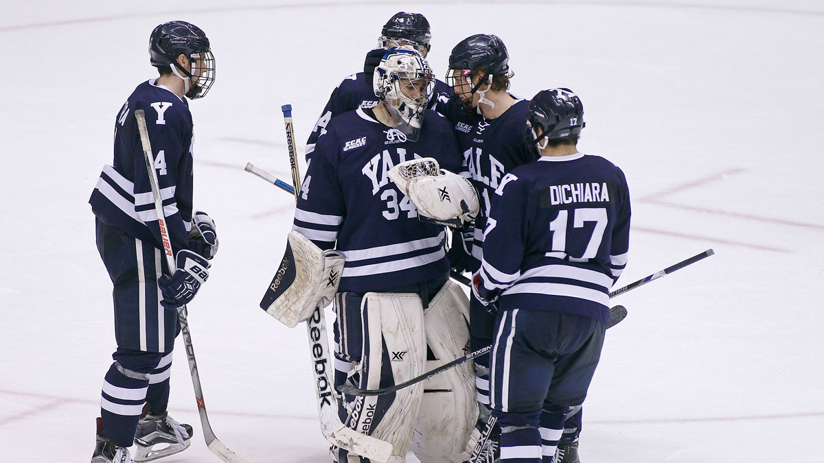 Yale goalie Alex Lyon (34) is congratulated by teammates Rob O'Gara (4), Ryan Obuchowski, top, John Hayden, center right, and Frankie DiChiara (17) after a 4-0 victory against Arizona State during an NCAA college hockey game at the Desert Hockey Classic tournament, Friday, Jan. 8, 2016, in Glendale, Ariz.