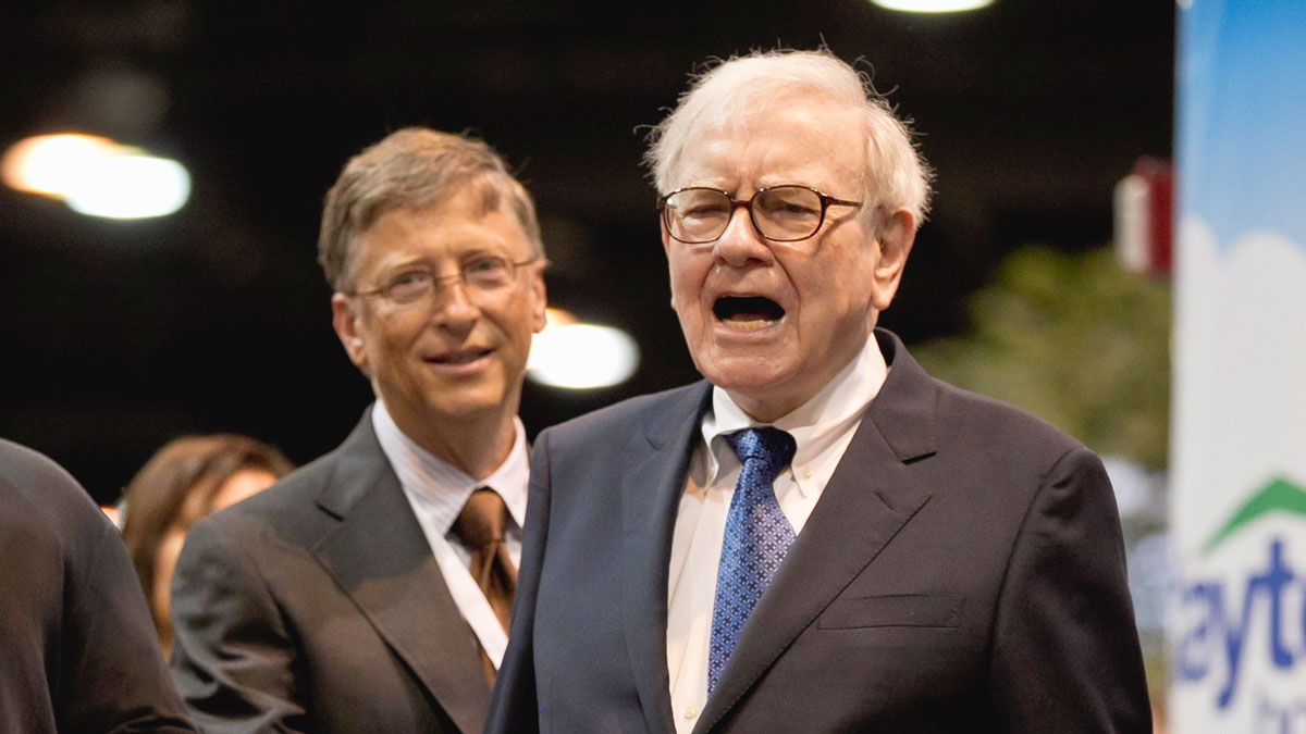 Warren Buffett, chairman and CEO of Berkshire Hathaway, right, reacts to a newspaper throw with Bill Gates, left, at the newspaper throwing competition prior to the Berkshire Hathaway shareholders meeting in Omaha, Neb., Saturday, May 5, 2012.