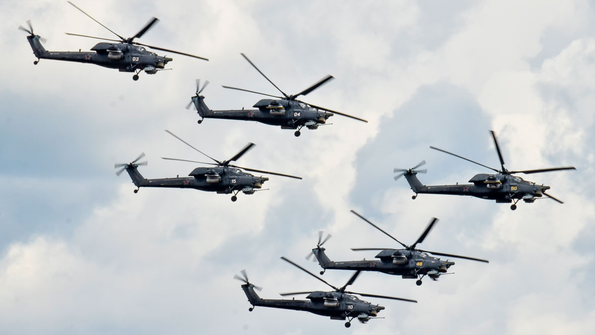 Russian military helicopters from an elite aerobatic squadron including no. 15, second left, fly during an air show in Dubrovichi, Russia, Sunday, Aug. 2, 2015, prior to one of the helicopters crashing. The Mi-28 helicopter gunship was part of a flight of helicopters performing aerobatics at the Dubrovichi firing range in Ryazan region, about 170 kilometers (105 miles) southeast of Moscow, when it crashed Sunday.