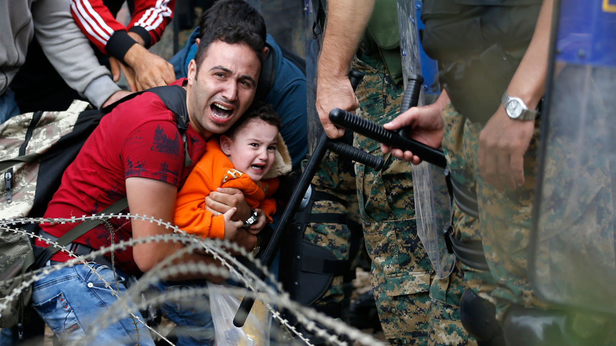 A migrant man holding a boy react as they are stuck between Macedonian riot police officers and migrants during a clash near the border train station of Idomeni, northern Greece, as they wait to be allowed by the Macedonian police to cross the border from Greece to Macedonia, Friday, Aug. 21, 2015. Macedonian special police forces have fired stun grenades to disperse thousands of migrants stuck on a no-man's land with Greece, a day after Macedonia declared a state of emergency on its borders to deal with a massive influx of migrants heading north to Europe.