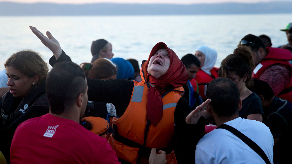 A woman reacts as she arrives aboard a dinghy after crossing from Turkey, to the island of Lesbos, Greece, on Saturday, Sept. 19, 2015. A girl about five years old died and at least 13 undocumented refugees and migrants were missing on Saturday after a boat transferring dozens of people from Turkey to Greece overturned off Lesbos island, Greek Coast Guard said.