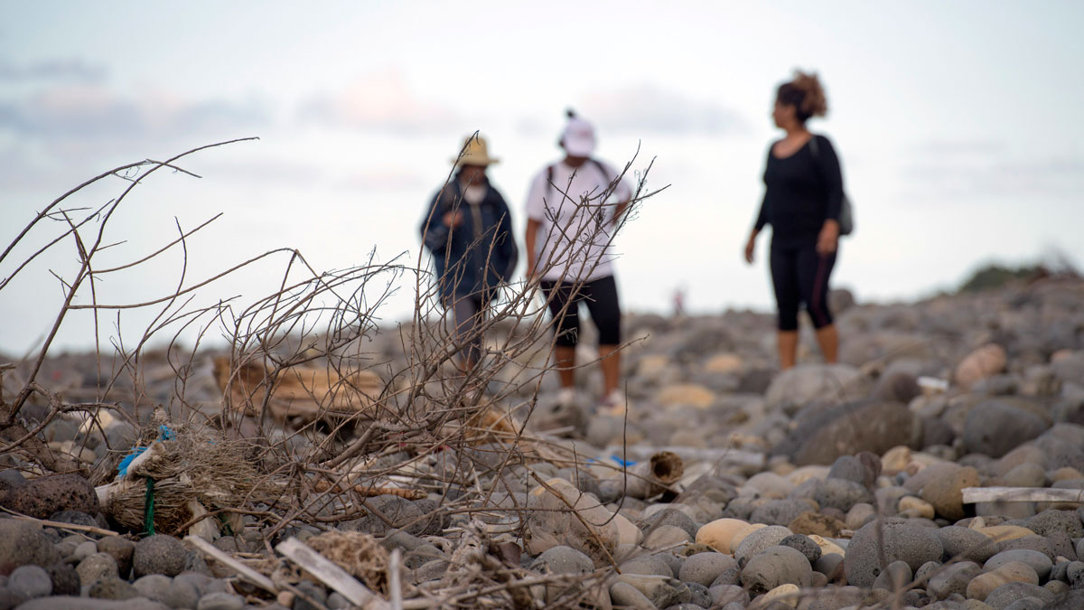 People walk on the beach of Saint-Andre, Reunion Island, in the hope of finding more plane debris, Thursday, July 30, 2015. A 6-foot long piece of an airplane was found off Reunion Island on Wednesday by people cleaning the beach. Air safety investigators, one of them a Boeing investigator, have identified the component as a