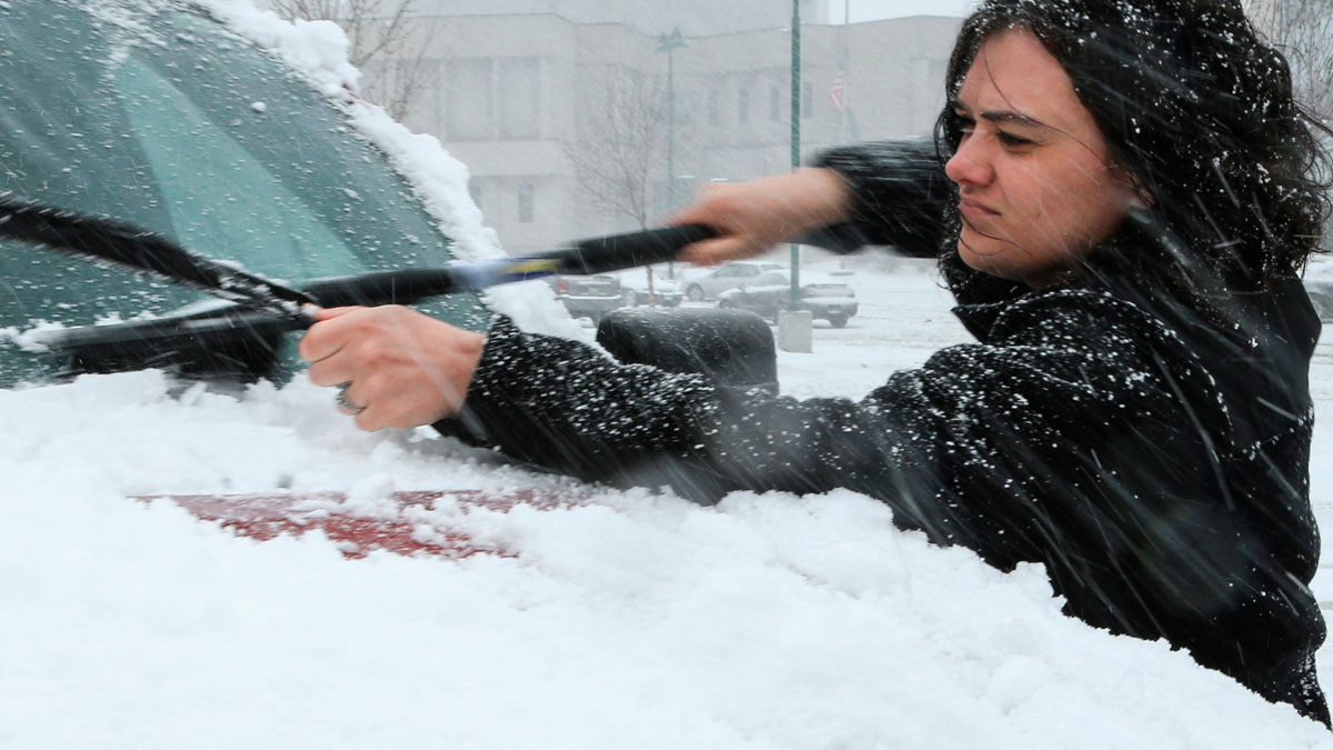 A woman clears snow off of her car in Sioux Falls, South Dakota, Wednesday, March 23, 2016. A powerful spring blizzard stranded travelers at Denver's airport and shut down hundreds of miles of highway in Colorado, Wyoming and Nebraska as it spread into the Midwest on Wednesday.