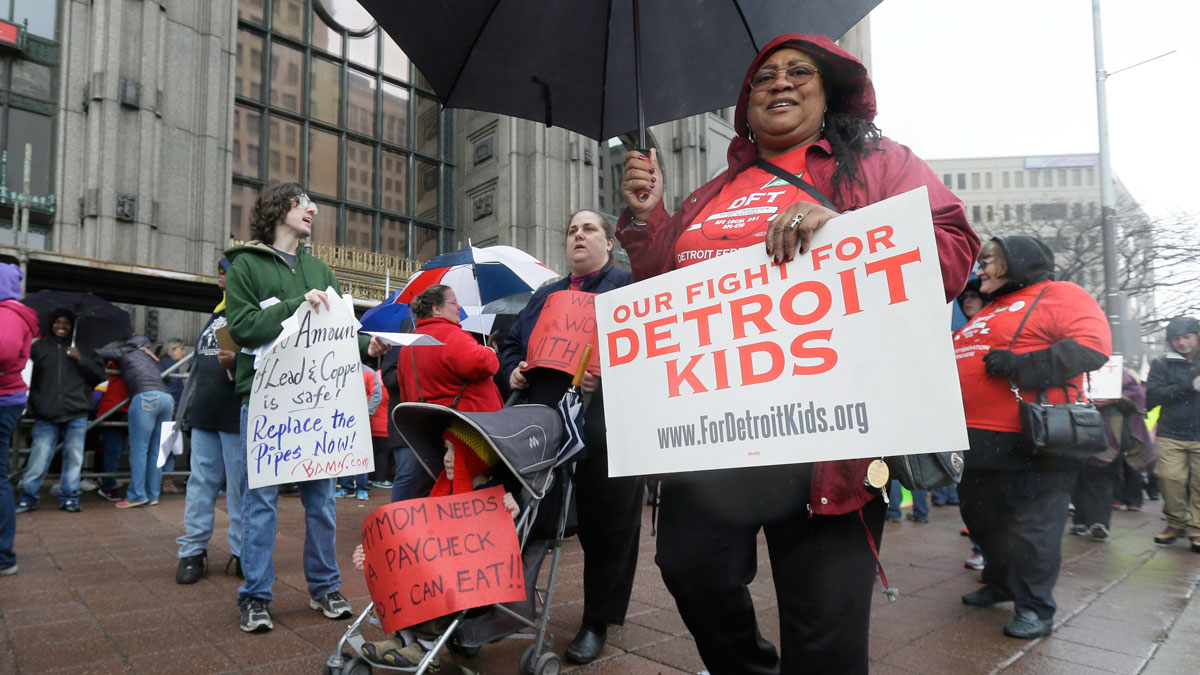 Detroit teachers march outside the district headquarters, Monday, May 2, 2016, in Detroit.