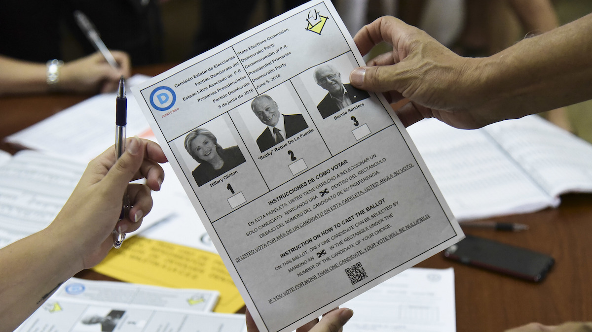 A Puerto Rico resident is handed a ballot during the U.S. territory's Democratic primary election at the Luis Llorens Torres Elementary School in San Juan, Puerto Rico, on June 5, 2016 . Puerto Ricans frustrated by island's economic crisis are voting in the U.S. territory's Democratic presidential primary, as front-runner Hillary Clinton draws closer to securing the number of delegates needed to win her party's nomination.