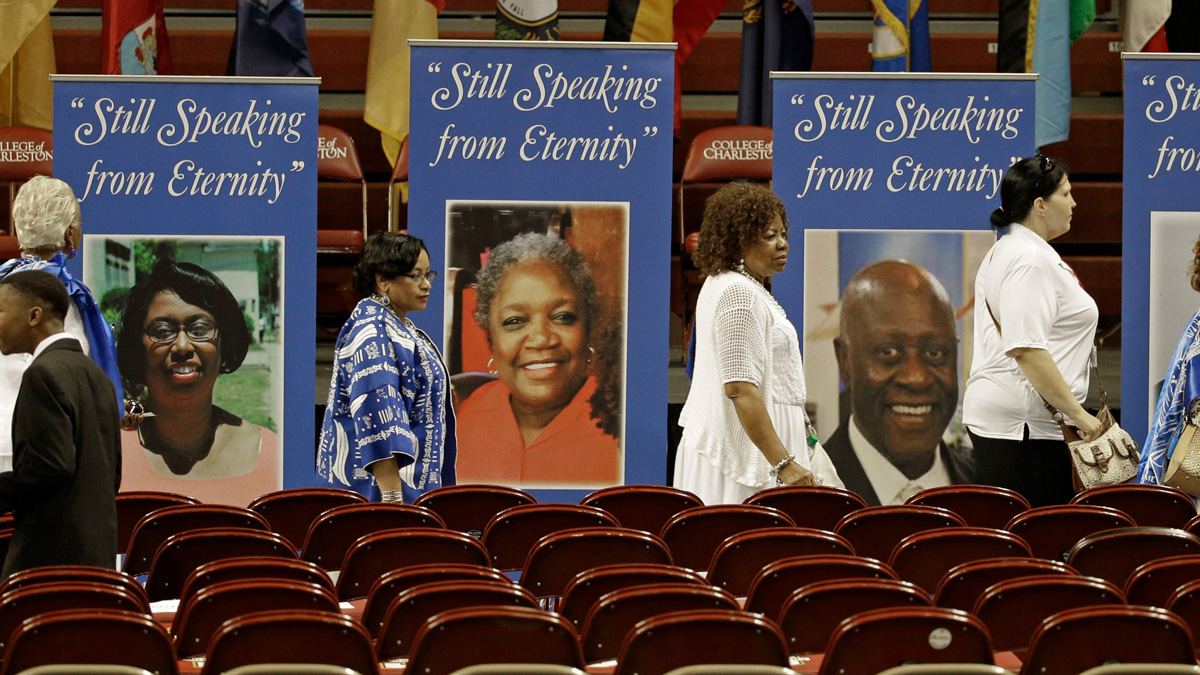 People walk past photos of some of the victims of the shooting at Mother Emanuel AME Church before a memorial service honoring those killed in Charleston, S.C., Friday, June 17, 2016.