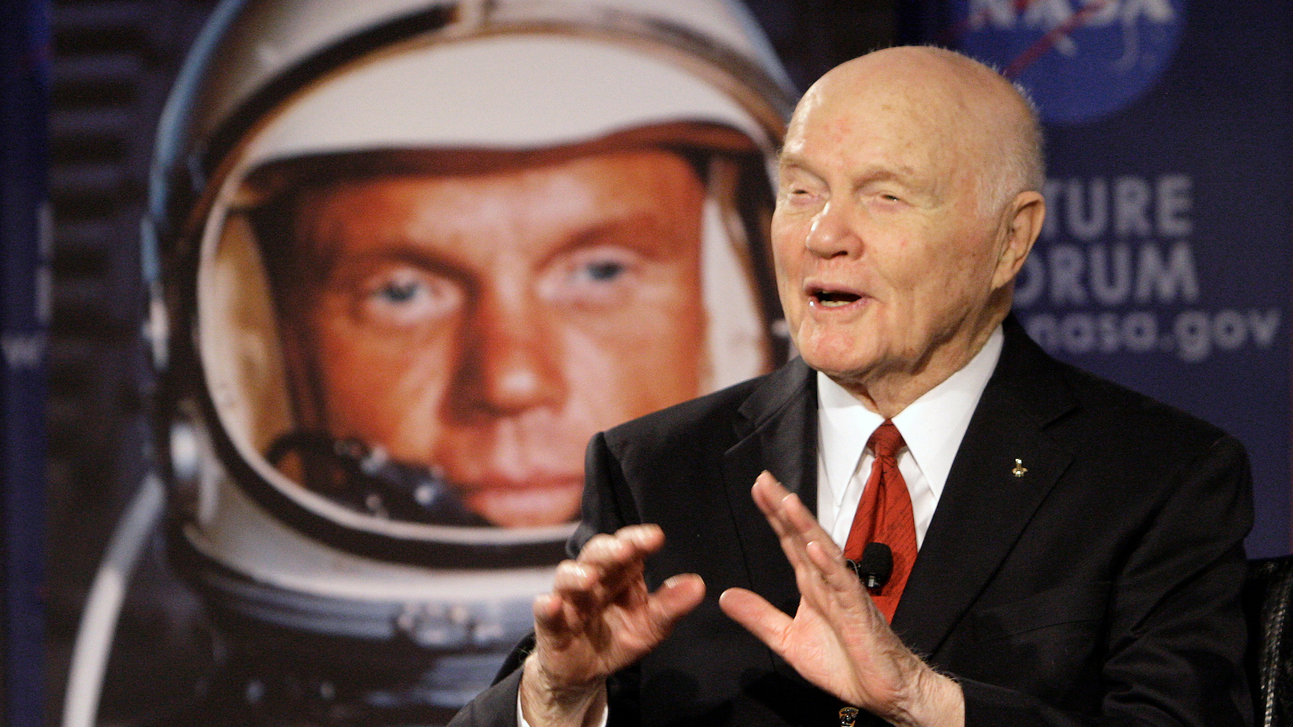 Former U.S. Sen. John Glenn talks with astronauts on the International Space Station via satellite before a discussion titled