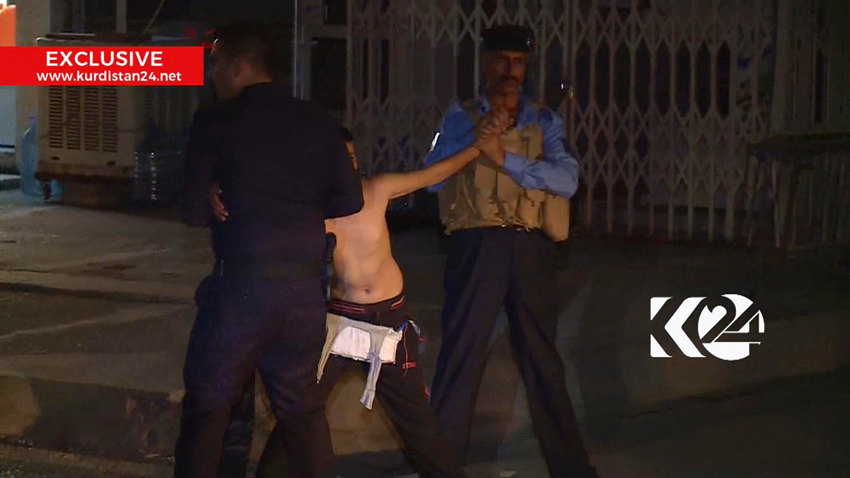 This still taken from local TV footage shows a child being restrained by security forces, holding his arms outstretched as another man cuts off a belt of explosives, Sunday Aug. 21, 2016, in Kirkuk, Iraq. Iraqi police say they apprehended the would-be suicide bomber before he was able to detonate his explosive belt.