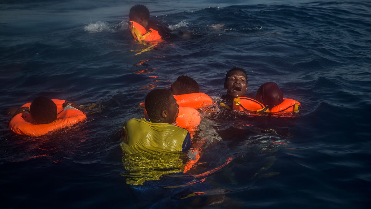 In this file photo taken on Sunday Sept. 11, 2016, six people are seen floating in the water after falling from the rubber boat departing Libya, during a rescue operation on the Mediterranean sea, about 18 miles north of Sabratha, Libya.