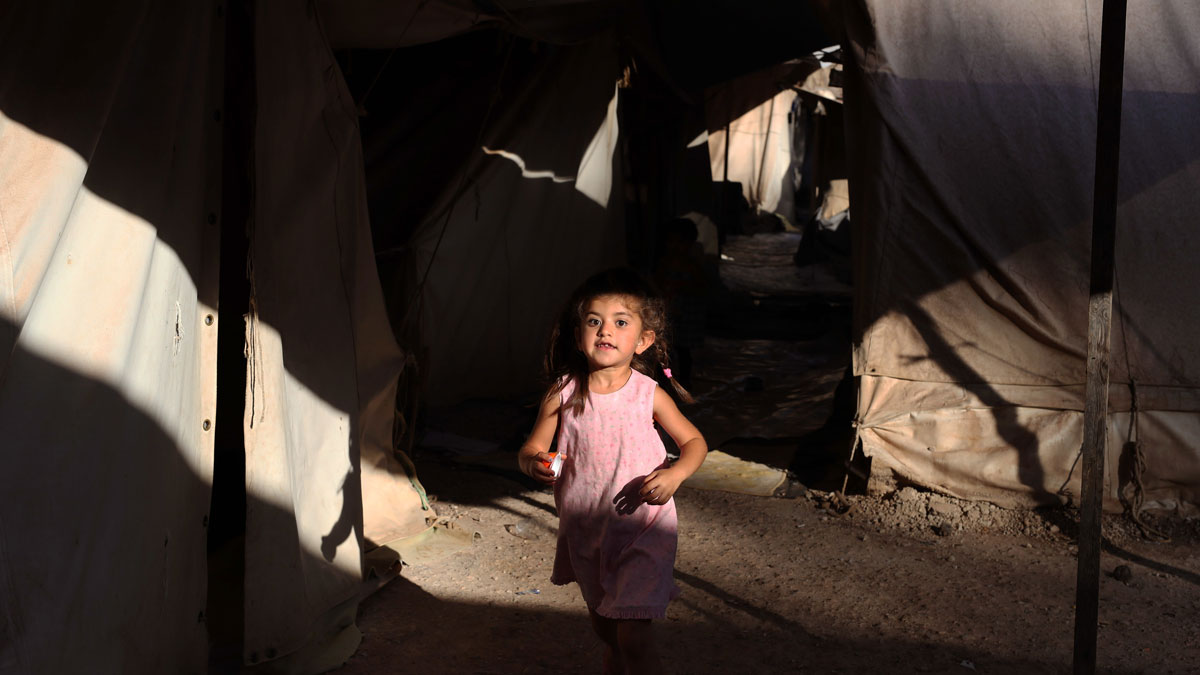 A little girl runs among tents as she plays with other children at Ritsona refugee camp, which hosts about 600 refugees and migrants, north of Athens, Monday, Sept. 12, 2016. The European Union will add 115 million euros ($129 million) in funding to humanitarian organizations in Greece to assist programs for refugees and migrants before the winter, officials said Saturday.