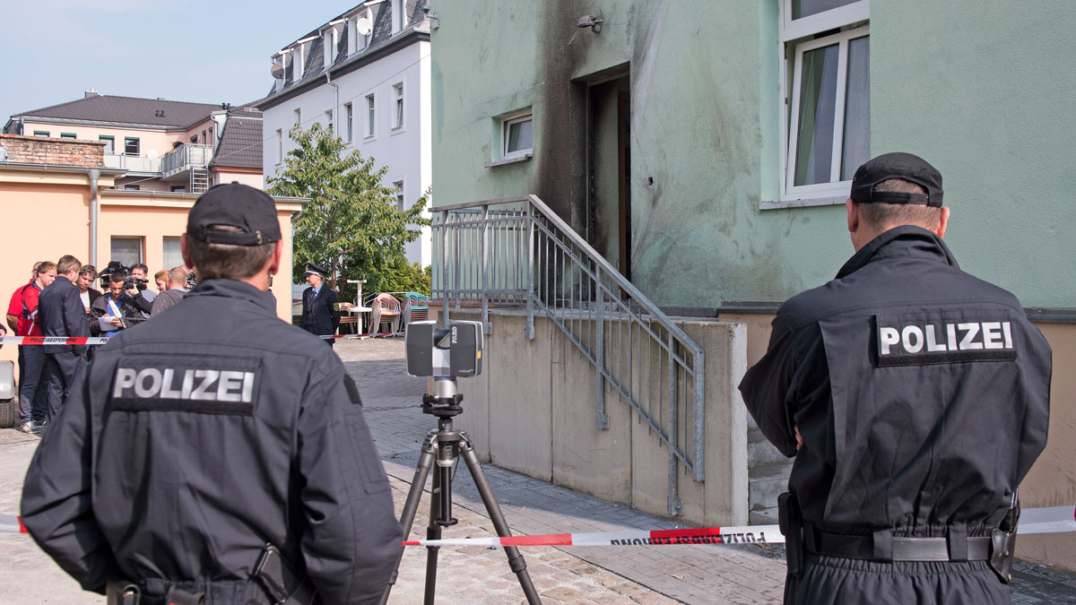 Policemen stand in front of the entrance of the Fatih Camii mosque in Dresden, eastern Germany, Tuesday, Sept. 27, 2016. Two bombs exploded in front of the mosque and an international congress building in Dresden the night before. Nobody was injured.