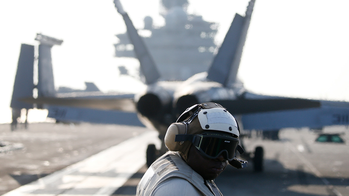 A U.S. Navy crew member looks at an F/A-18 Super Hornet fighter as it prepares to take off from the USS Ronald Reagan, a Nimitz-class nuclear-powered super carrier, during a joint naval drill between South Korea and the U.S. in the West Sea, South Korea, Friday, Oct. 14, 2016.