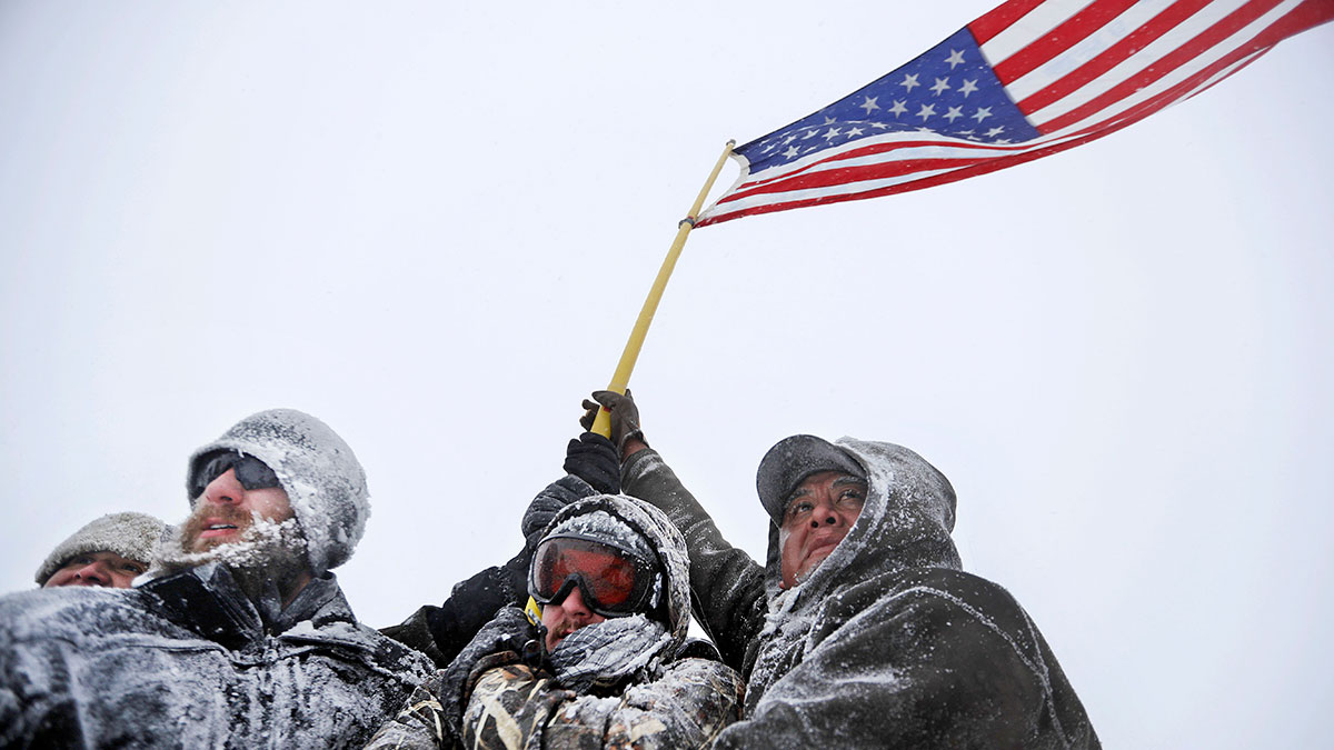 Military veterans huddle together to hold a United States flag against strong winds during a march to a closed bridge outside the Oceti Sakowin camp where people have gathered to protest the Dakota Access oil pipeline in Cannon Ball, N.D., Monday, Dec. 5, 2016.