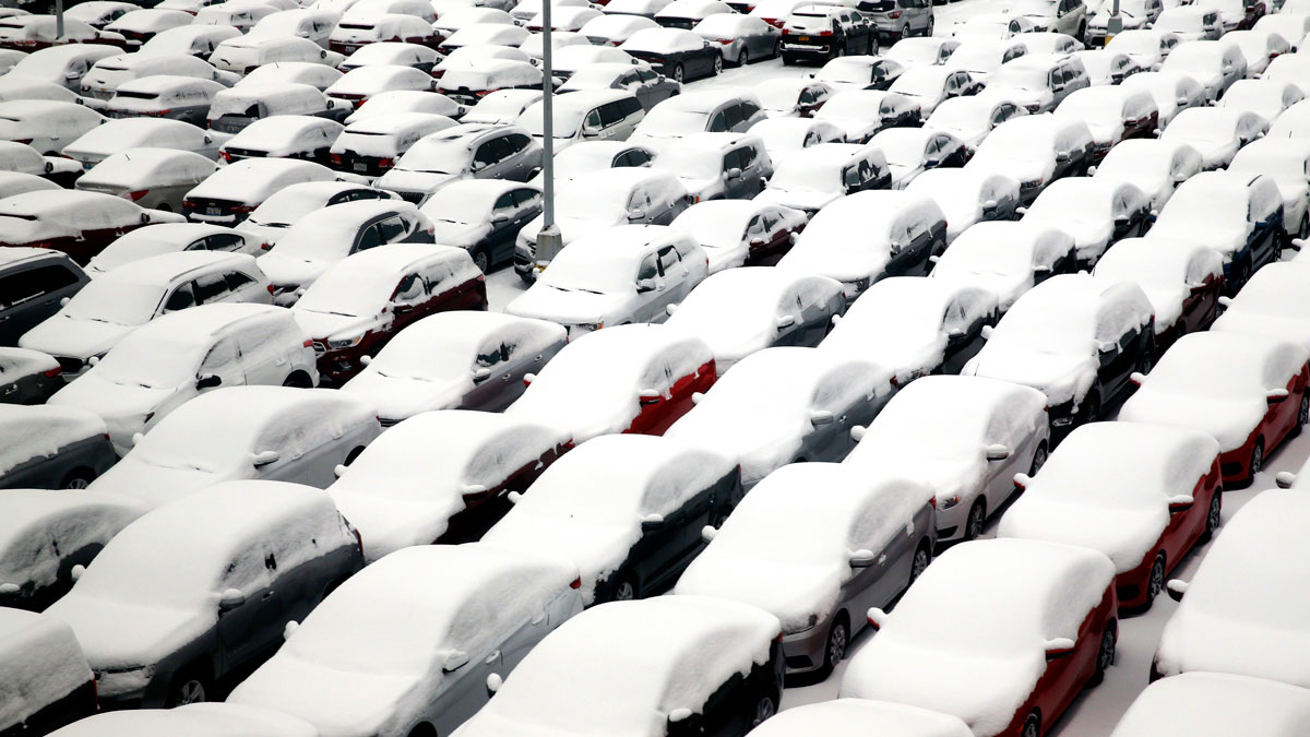 Snow covers vehicles in a rental car parking lot at O'Hare International Airport, Dec. 11, 2016, in Chicago.