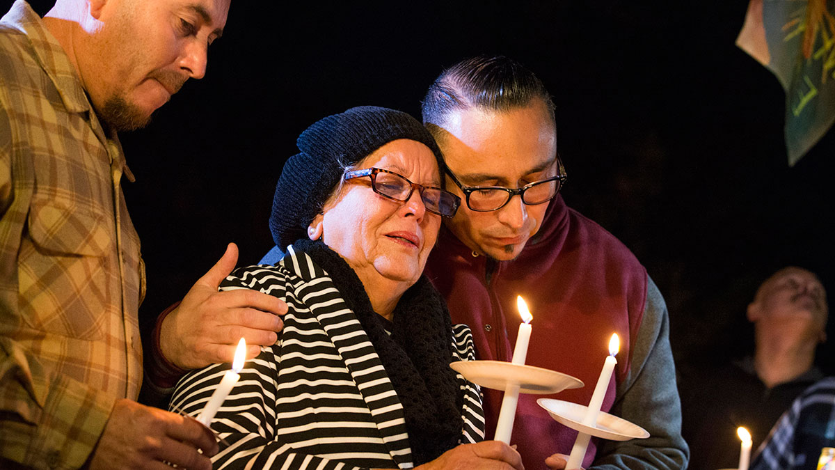 In this photo provided by The Bakersfield Californian, Rubia Serna is consoled by her sons Jesse Serna, right, and Frank Serna at the candlelight vigil for Francisco Serna, 73, her husband and their father, Tuesday, Dec. 13, 2016, in Bakersfield, California.