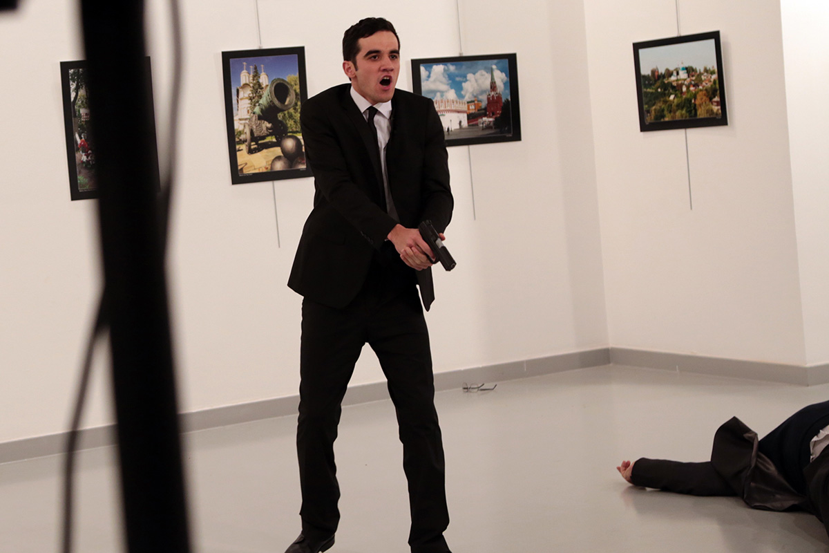 Mevlut Mert Altintas shouts after shooting the Russian Ambassador to Turkey, Andrei Karlov, at a photo gallery in Ankara, Turkey, Monday, Dec. 19, 2016. A Russian official says that the country's ambassador to Turkey has died after being shot by a gunman in Ankara.