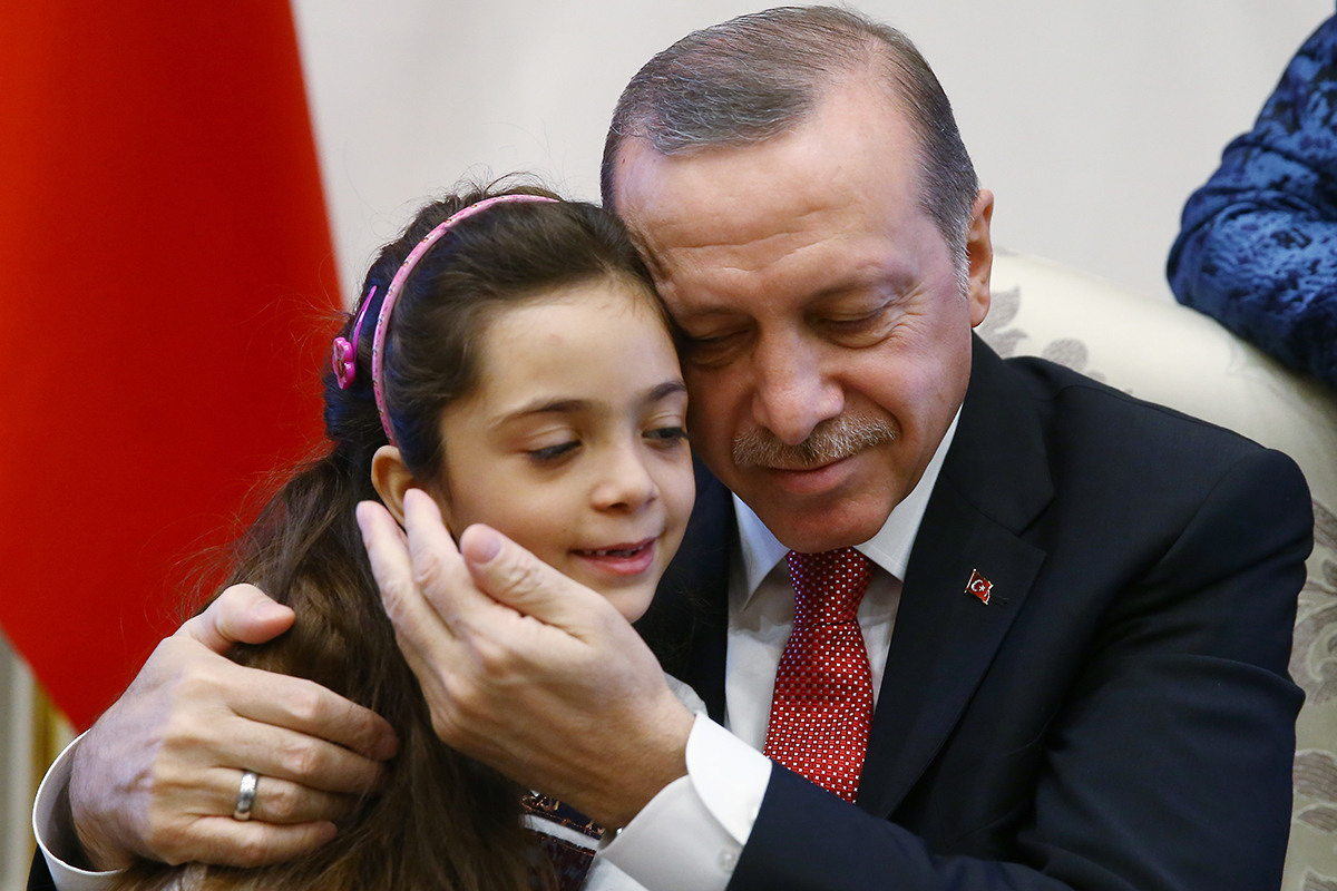Turkey's President Recep Tayyip Erdogan embraces Bana Al-Abed, 7, from Aleppo, Syria, at his Presidential Palace in Ankara, Turkey, Wednesday, Dec. 21, 2016. Al-Abed became the face of civilian life in Aleppo when her tweets of life under siege went viral.