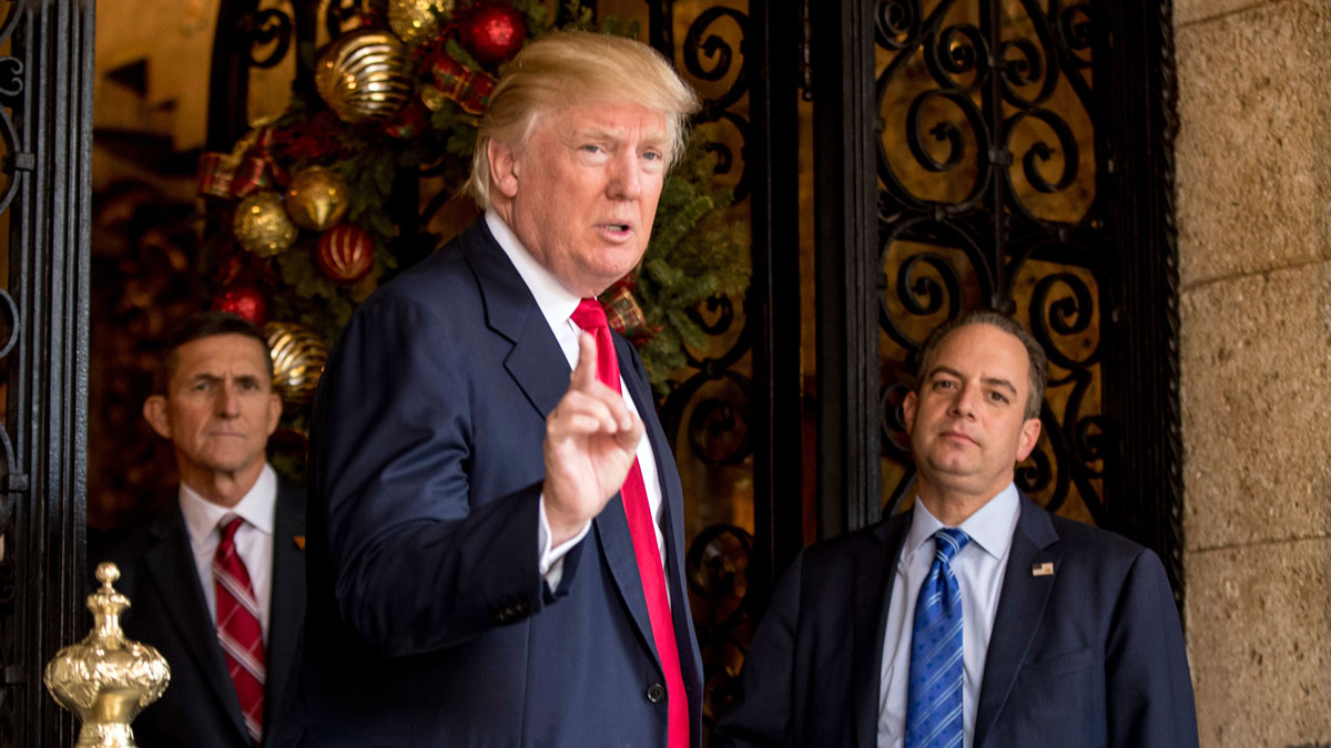 President-elect Donald Trump, center, accompanied by Trump Chief of Staff Reince Priebus, right, and retired Gen. Michael Flynn, a senior adviser to Trump, left, speaks to members of the media at Mar-a-Lago, in Palm Beach, Fla., Wednesday, Dec. 21, 2016.