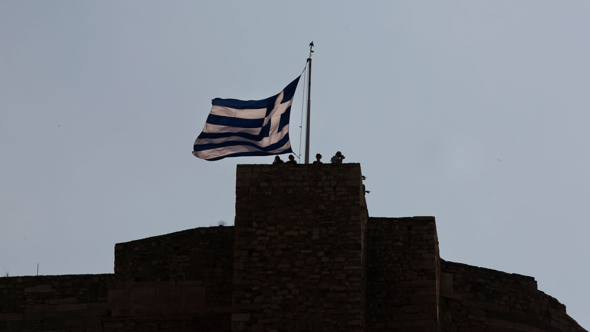 Tourist stand above a huge Greek flag at the top of the Acropolis hill in Athens, Saturday, July 11, 2015. Greece's negotiators head to Brussels on Saturday armed with their reform proposals and parliamentary backing to seek a third bailout, but with the shadow of severe dissent from governing lawmakers hanging over them.