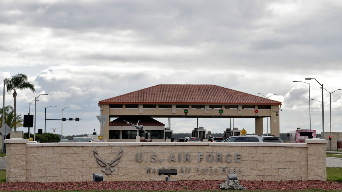 The main gate at MacDill Air Force Base Friday, Jan. 13, 2017, in Tampa, Florida. On any given day at MacDill, web crawlers anonymously scour social media for potential recruits to the Islamic State group. Then, in a high-stakes operation to counter the extremists' propaganda, language specialists employ fictitious identities and try to sway the targets from joining IS ranks. At least, that's how a new multimillion-dollar contract is being sold to the Defense Department. (AP Photo/Chris O'Meara)