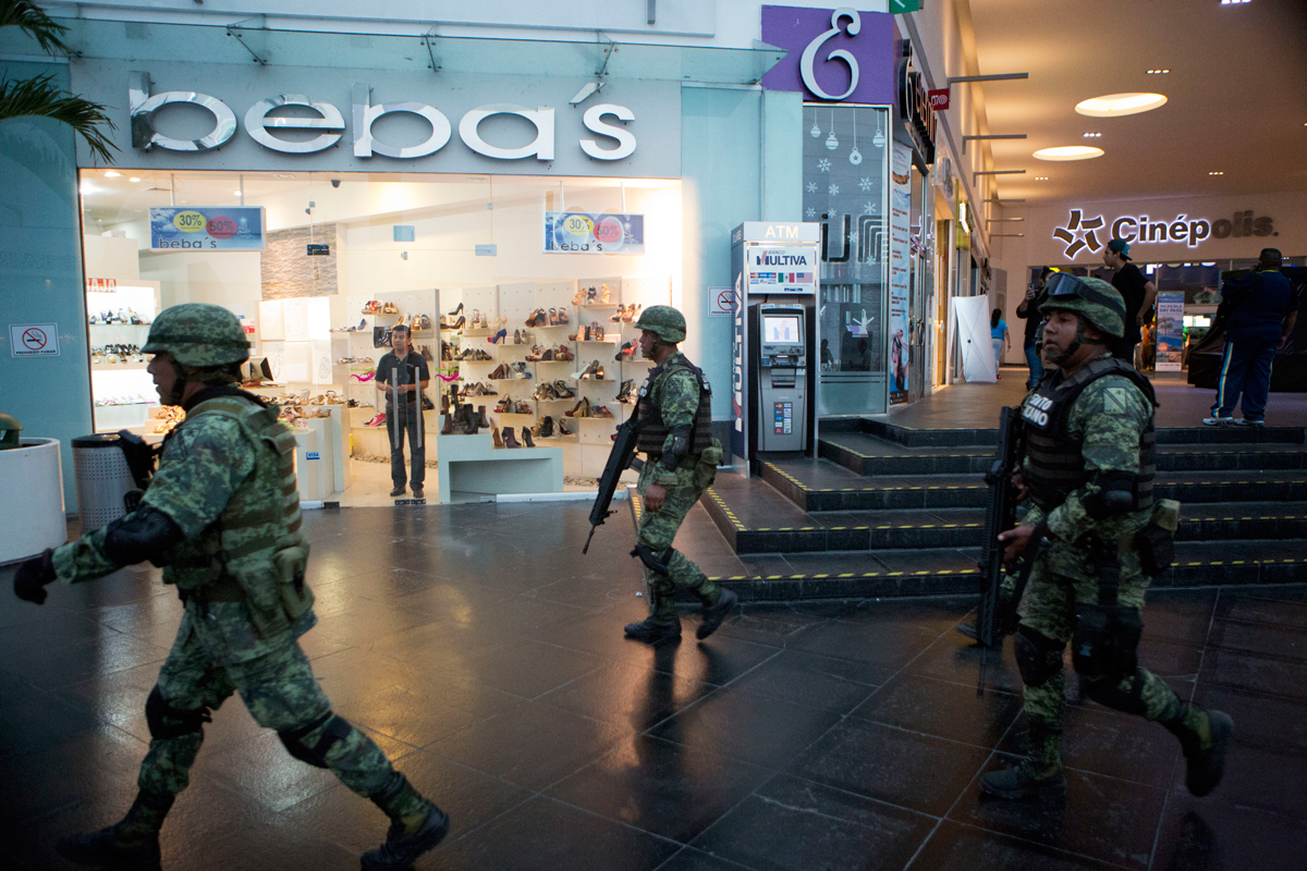 Soldiers walk inside Plaza Las Americas mall following reports of gunfire in Cancun, Mexico, Jan. 17, 2017. The U.S. State Department issued an updated travel advisory for citizens traveling to Mexico, expanding a Dec. 8 warning to include the state of Quintana Roo, home to several resorts popular with American tourists.