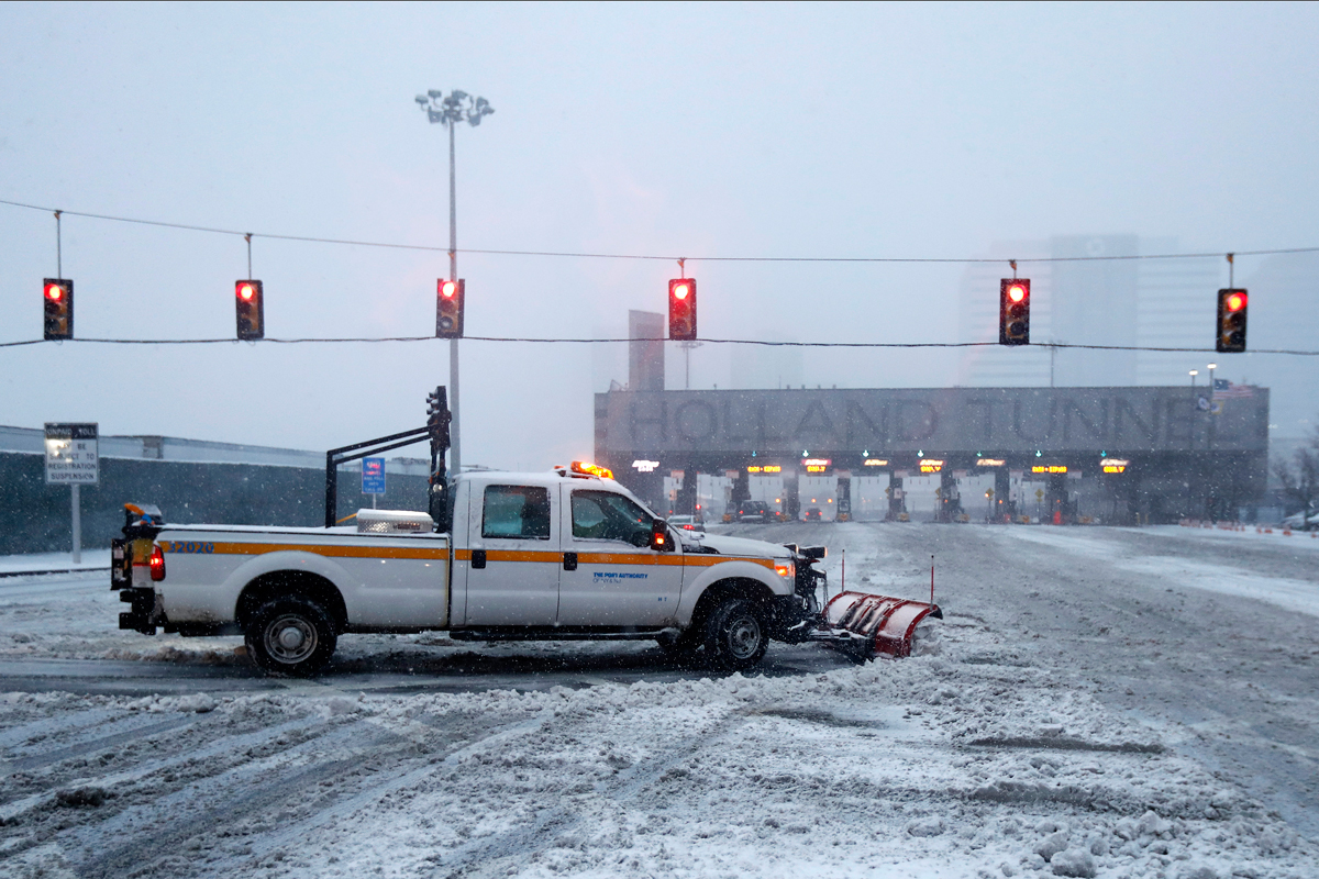 A Port Authority of New York and New Jersey truck plows snow near the Holland Tunnel approach during a snowstorm, Feb. 9, 2017, in Jersey City, N.J.