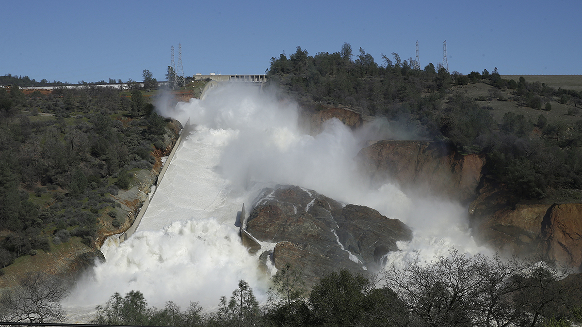 In this Saturday, Feb. 11, 2017, water flows down Oroville Dam's main spillway near Oroville, Calif. Officials have ordered residents near the Oroville Dam in Northern California to evacuate the area Sunday, Feb. 12, saying a