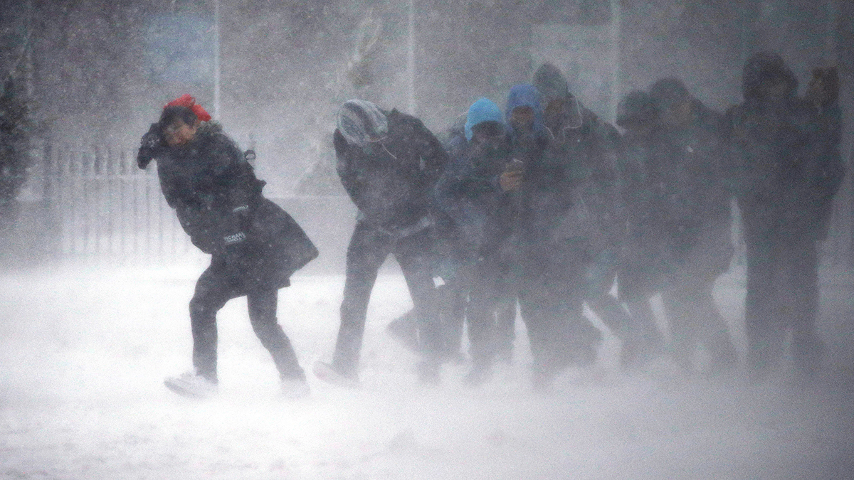 People struggle to walk in the blowing snow during a winter storm Tuesday, March 14, 2017, in Boston.