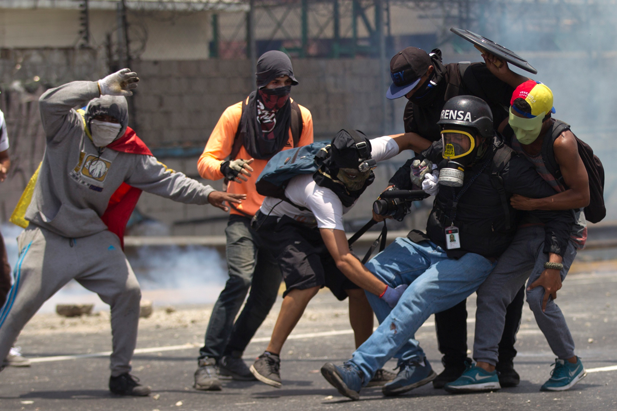Demonstrators help an injured journalist who was covering clashes between demonstrators and the Bolivarian National Guard during a protest in Caracas, Venezuela, April 10, 2017. Opponents of President Nicolas Maduro protested on the streets of the capital as part of an ongoing movement that shows little sign of losing steam.