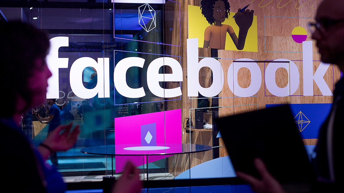 Conference workers speak in front of a demo booth at Facebook's annual F8 developer conference, Tuesday, April 18, 2017, in San Jose, Calif.