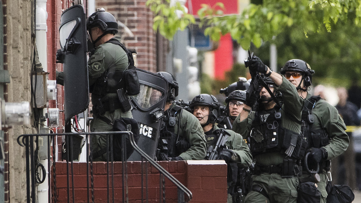 Police move during standoff with a man is a home in Trenton, N.J, Wednesday, May 10, 2017. Police are trying to negotiate with a man holed up in a home in New Jersey's capital city after they say he exchanged gunfire with police, killing one person.
