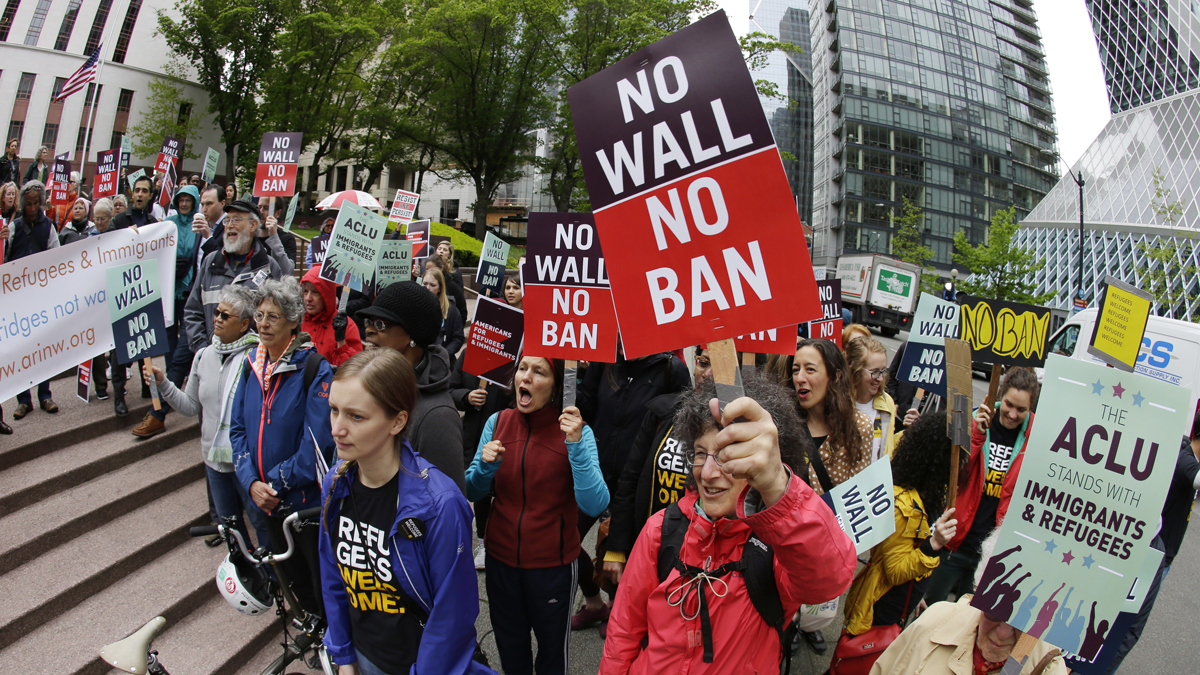 Protesters wave signs and chant during a demonstration against President Donald Trump's revised travel ban, Monday, May 15, 2017, outside a federal courthouse in Seattle.